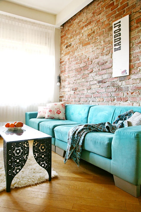 an eclectic living room with a turquoise sofa, a red brick wall and a refined coffee table