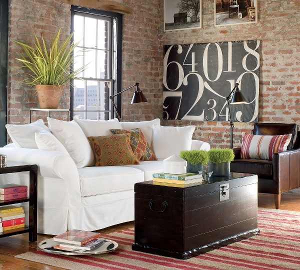 a boho chic living room with muted red brick walls, boho textiles and potted greenery