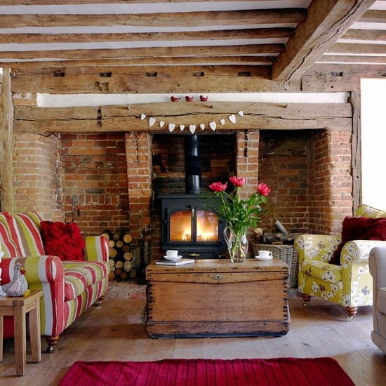 a rustic living room with a red brick wall and much wood in decor, with colorful upholstery furniture