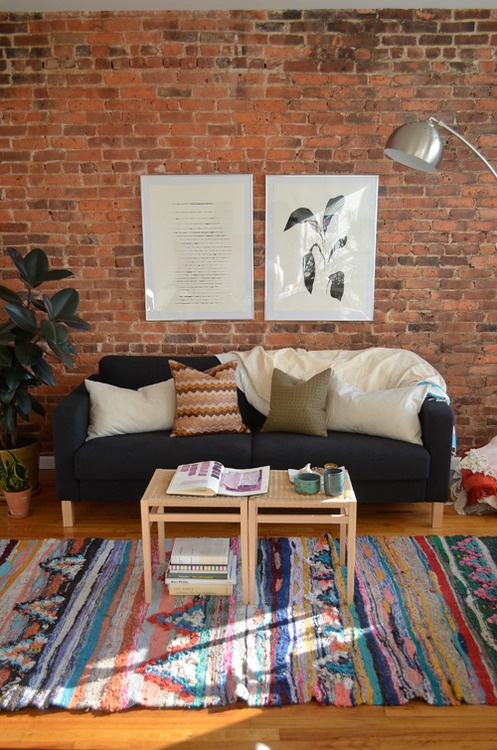 a bright boho chic living room with a red brick wall and colorful rugs and textiles
