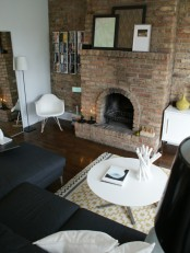 a black and white living room is spruced up with a textural brick statement wall – it adds color and texture