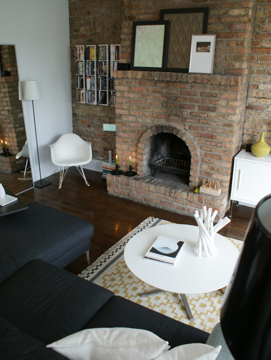 a black and white living room is spruced up with a textural brick statement wall - it adds color and texture