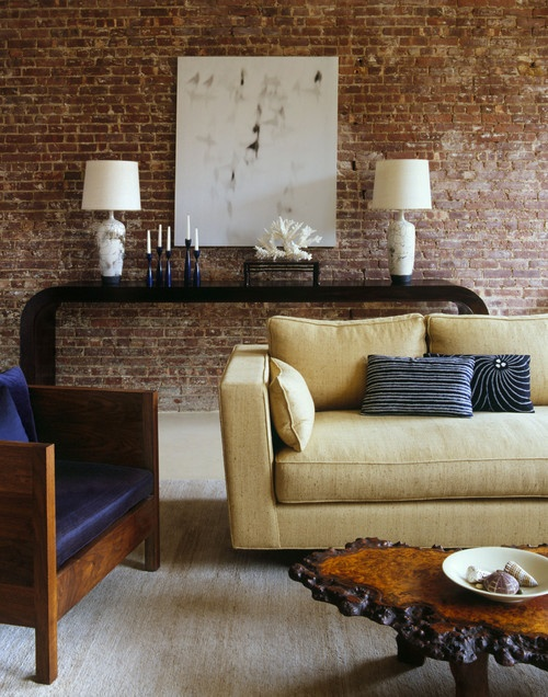 a refined living room is made less formal with a red brick statement wall, which also brings texture