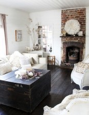 a black and white farmhouse living room with a red brick statement fireplace, which adds color and coziness to the space