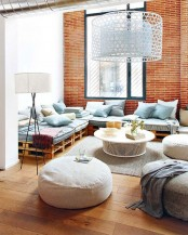 an eclectic living room with bright orange brick walls and contrasting blue furniture and large lampshades