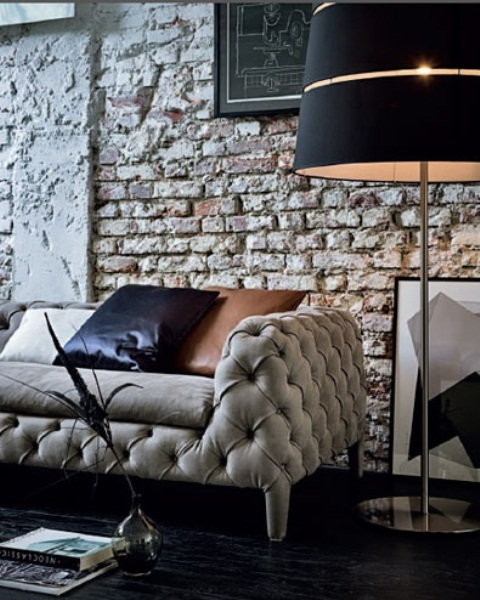 a luxurious and refined living room in black and white with a rough brick statement wall