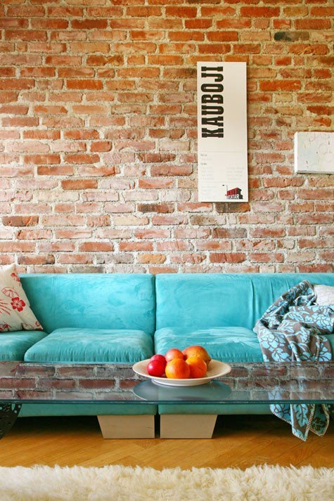 a red brick statement wall contrasts the bright turquoise sofa and a glass coffee table