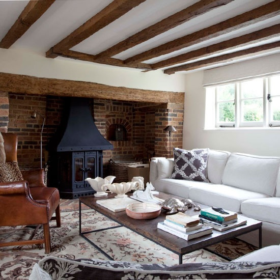 a refined and chic living room in neutrals and spruced up with a black hearth and a red brick statement wall