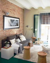 a contemporary living room with a red brick statement wall for more texture and interest