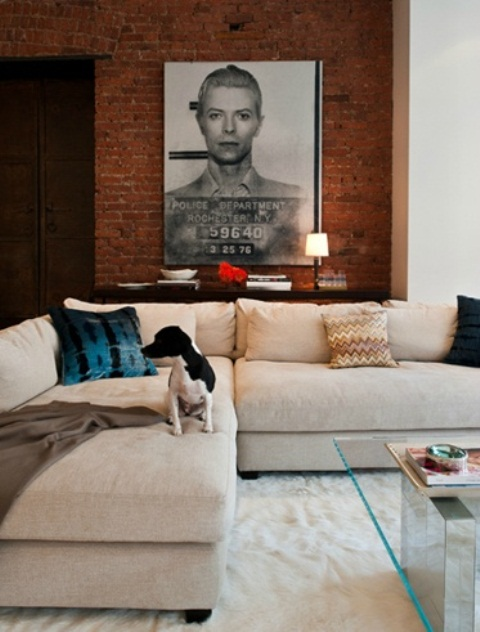 a contemporary living room with neutral upholstered furniture and a red brick statement wall that contrasts