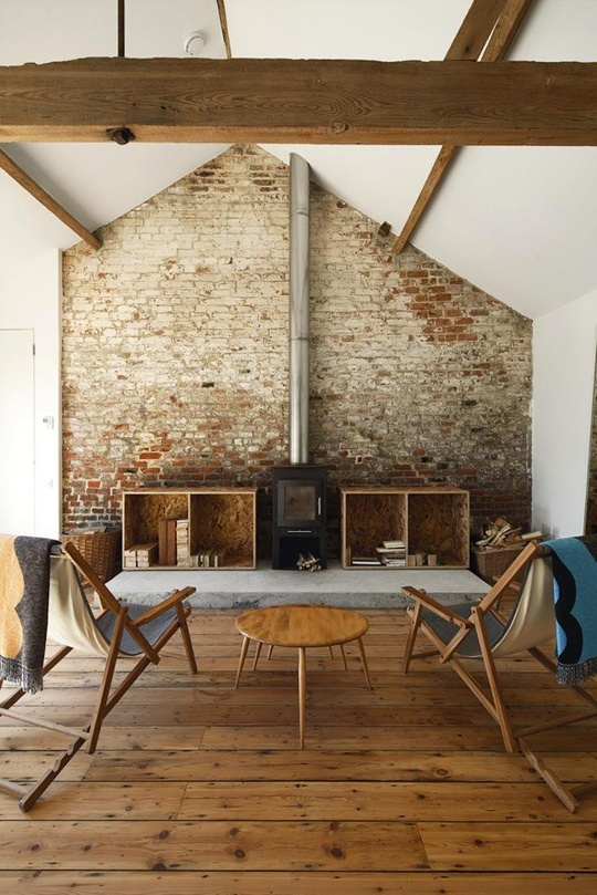 a rustic industrial living room with a rough brick wall and wooden beams that make up a character