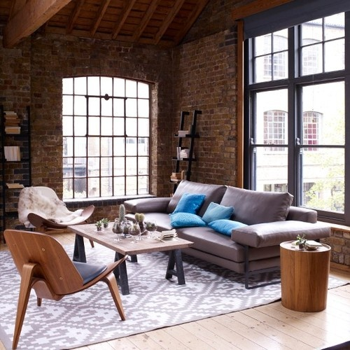 rough brick walls contrast the soft and neutral upholstered furniture and pillows