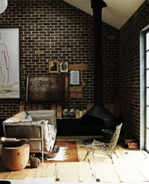a moody living room with dark brick walls with white grout and a black suspended fireplace plus rugs and wood