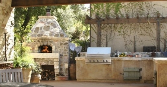 a traditional outdoor kitchen of stone with a grill and a pizza oven plus greenery around