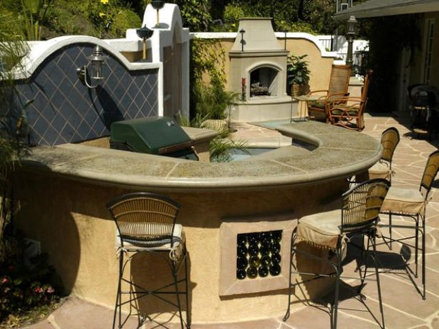 a comfortable dining area built of stone, with a stoen countertop and a grill inside it plus a hearth next to it