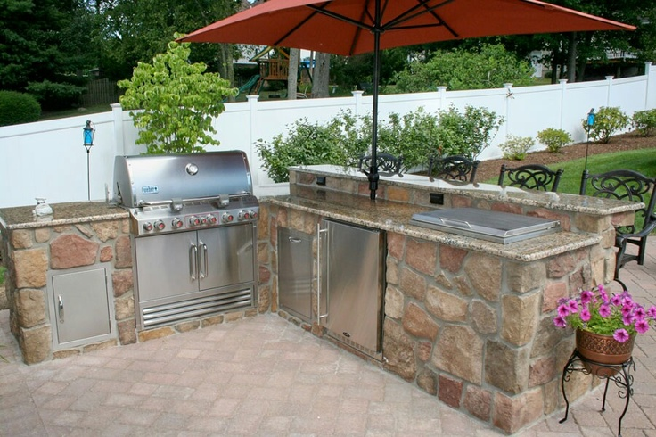 a simple and stylish outdoor kitchen built of stone and metal with a grill, a cooler and cooking coutnertops