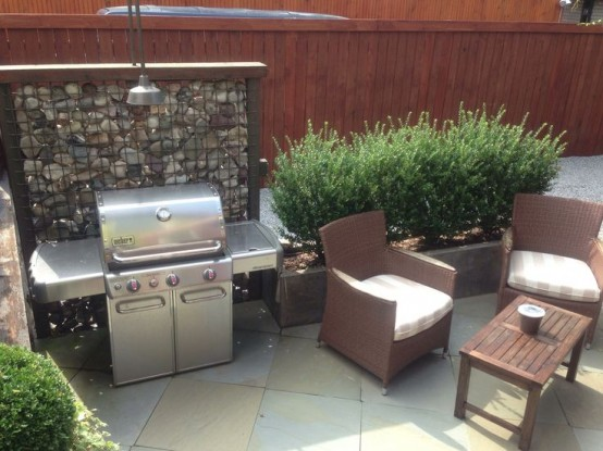 a simple outdoor bbq area with a grill, a couple of chairs and a coffee table plus greenery around