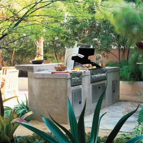an outdoor kitchen with concrete and metal with a grill and a raised top for having a meal