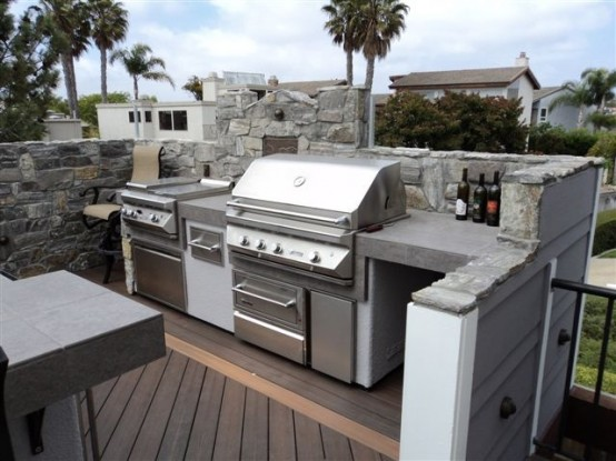 an outdoor kitchen built of stone, concrete and metal with a cooker and a grill for comfortable cooking