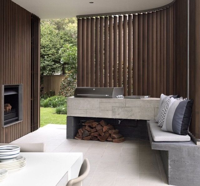 a minimalist bbq area with a concrete countertop flowing into a bench, with a grill on top and some firewood underneath