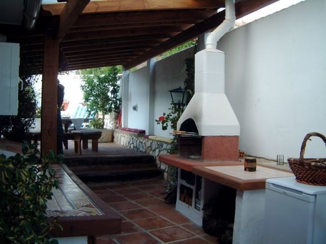 an outdoor cooking zone with a cooking top and a hearth for cooking