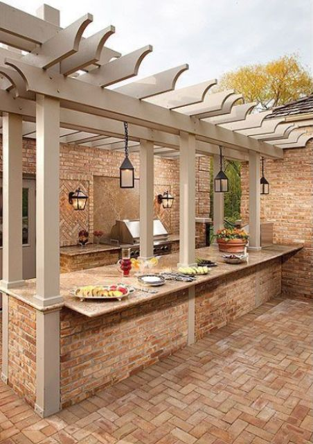 an outdoor bbq zone built of stone and brick, with a grill, lanterns, a cooking countertop and a meal space