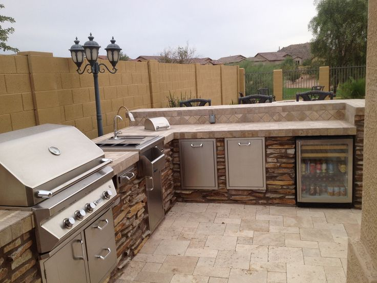 an outdoor bbq area of stone and tiles, with a cooking countertop, a sink and a grill