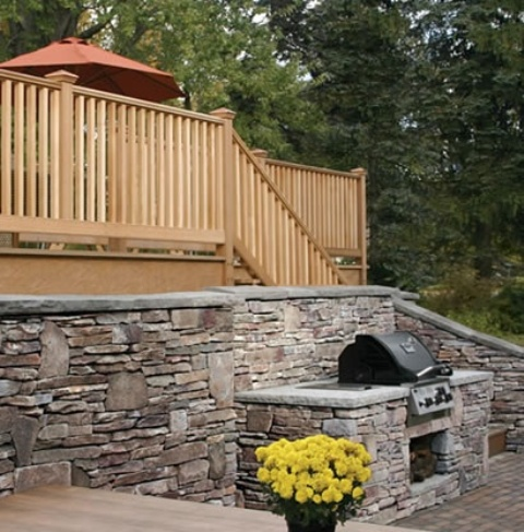 a traditional outdoor bbq zone with a stone wall and bbq countertop plus a grill and a table for eating