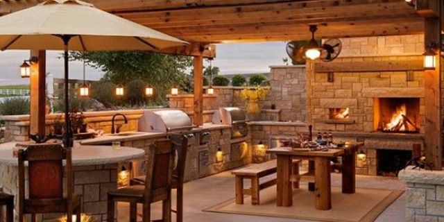 a cozy rustic outdoor bbq area of stone and wood, a sink, a grill, a fireplace and a dining zone next to it