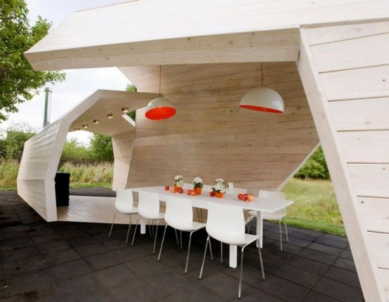 a minimalist dining area inside a sculptural pavilion with lights and a stylish minimal dining set in white