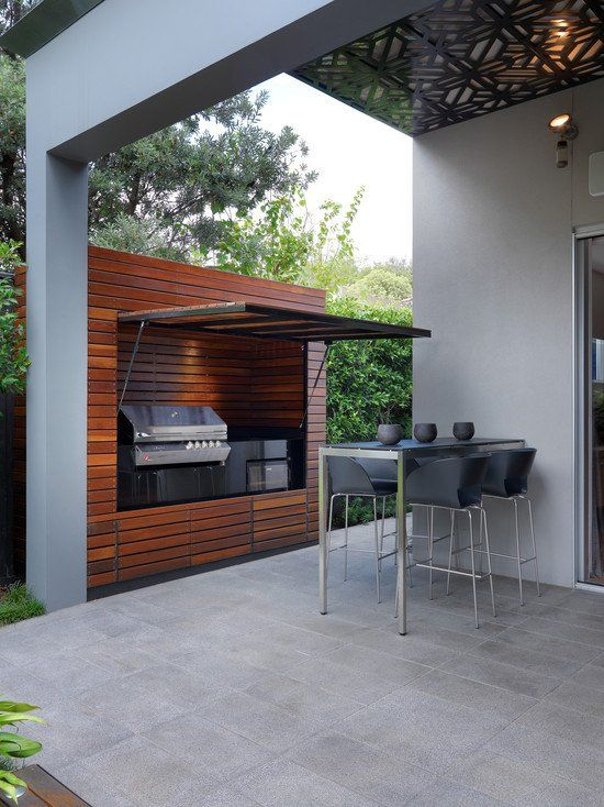 a minimalist outdoor bbq area with a dining set in black and a grill plus a cooker inside a wooden unit