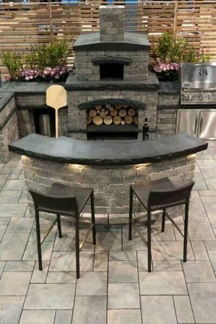 a dark bbq area of stone and bricks, with black countertops, a grill and a pizza oven plus a dining space