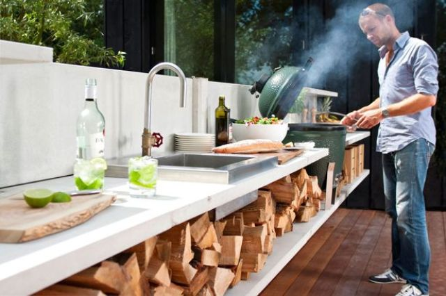 a contemporary outdoor kitchen with firewood storage, a sink, a cooking zone and a grill