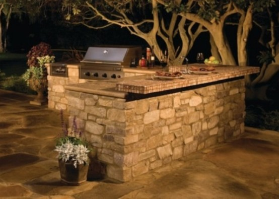 a simple outdoor kitchen clad with stone and with countertops plus a grill for cooking