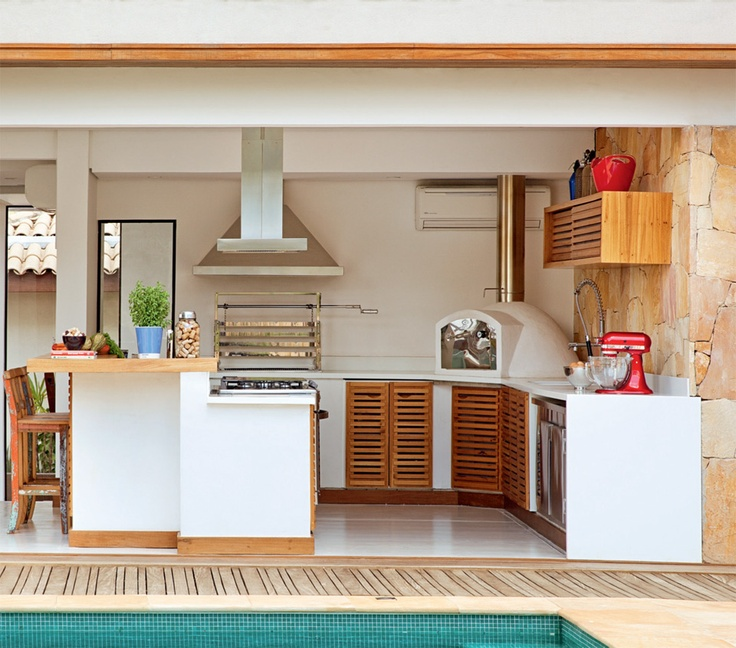a minimalist outdoor kitchen with white cabinets and wooden doors, a hood and a grill plus an additional eating space