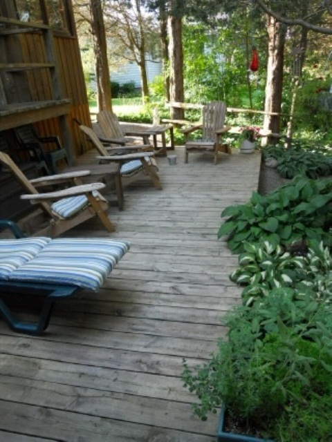 a rustic deck with wooden chairs and loungers, striped cushions and pillows and greenery around