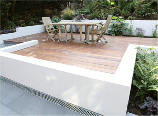a contemporary deck with wooden floors and simple rustic furniture for dining, some planted greenery around