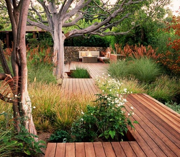 a contemporary deck with grasses growing and a cozy sittign room in the corner, a fireplace and some trees