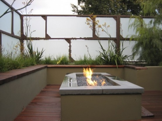 a contemporary deck with a white and wood walls for some privacy, a built-in bench, a fire pit and some grasses growing around