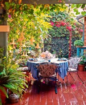 a colorful shabby chic deck with a forged garden furniture set, growing tress and greenery and colorful textiles