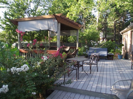 a rustic deck with weathered wood floors, rustic furniture, a bench, a gazebo and potted blooms and greenery