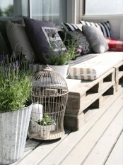 a Scandinavian deck with a pallet sofa, lots of pillows, a cage for decor and potted greenery and blooms