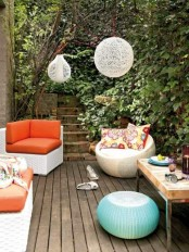 a welcoming and bright deck with a weathered wood floor, colorful furniture, yarn lamps and a cocktail table