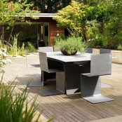 a minimalist deck with metal furniture of geometric shapes and much greenery around looks dreamy