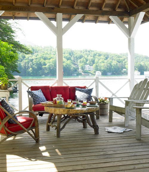 a rustic and relaxed deck with rattan and whtewashed wooden furniture, colorful textiles, a living edge table with food and drinks