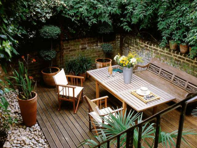a cozy rustic deck with simple wooden furniture, pebbles and potted greenery plus greenery all around for privacy