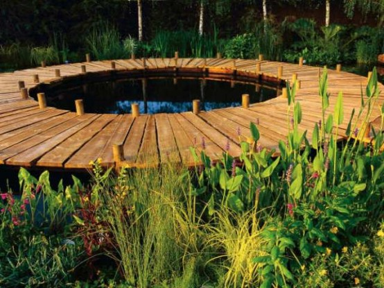 a simple round wooden deck with a pond inside it and lots of greenery around