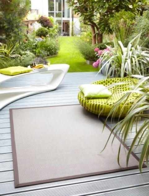 a contemporary deck with a sculptural console, a bright neon chair, a rug and growing greenery and blooms