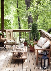 a small and cozy deck with simple wooden furniture, wicker accents, potted greenery and blooms and lanterns