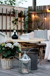 a contemporary deck with rattan furniture, lanterns, watering cans, potted greenery and blooms